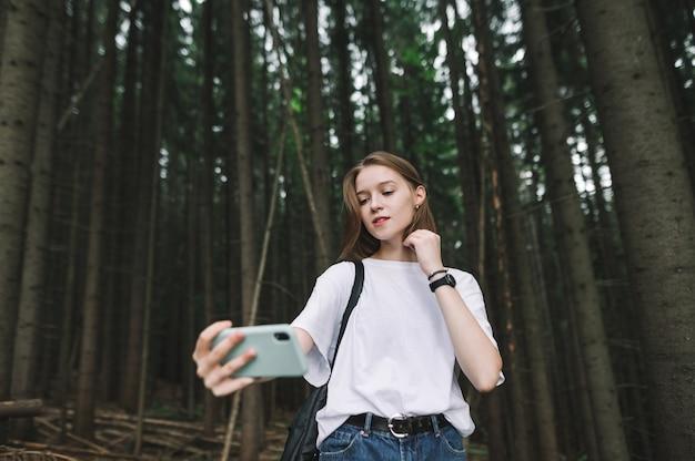 Donna turistica abbastanza elegante che utilizza la fotocamera del telefono per fare un selfie nella foresta di abeti di montagna