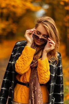 Giovane donna abbastanza elegante in abito estivo alla moda in occhiali da sole di moda in cappello di paglia vintage con labbra sexy in posa all'aperto in città. attraente ragazza europea in abito a righe alla moda all'aperto