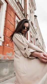 Piuttosto elegante giovane donna in occhiali da sole alla moda in impermeabile alla moda primavera beige gira su strada vicino a edificio d'epoca. modello di moda bella ragazza abbastanza moderna in abiti alla moda passeggiate in città.