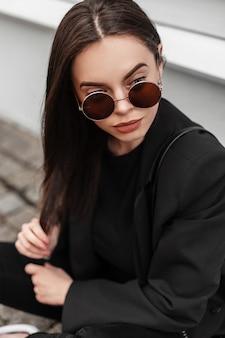 La giovane donna abbastanza alla moda in vestiti neri alla moda della gioventù in occhiali da sole posa vicino alla costruzione di legno in città. la modella americana della ragazza si siede sulla strada di pietra sulla strada. nuova collezione di moda giovanile.