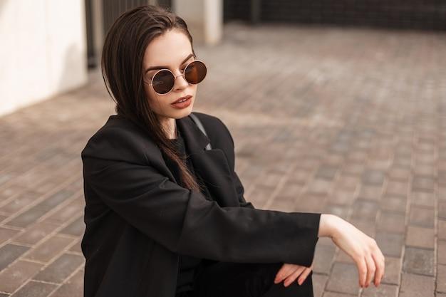 La giovane donna abbastanza alla moda in vestiti neri alla moda della gioventù in occhiali da sole si siede sulle mattonelle dell'annata in città. resto del modello di moda della ragazza americana sulla strada di pietra sulla via. nuova collezione di moda giovanile.