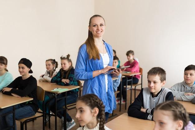 Insegnante grazioso che sorride alla macchina fotografica
