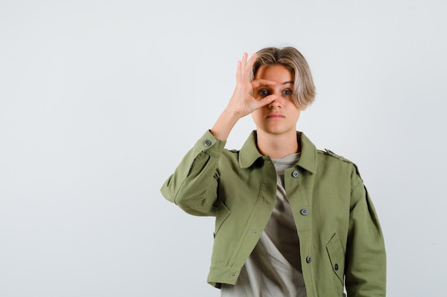Ragazzo abbastanza teenager che guarda attraverso le dita in giacca verde e sembra curioso, vista frontale.
