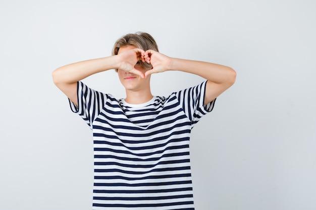 Ragazzo abbastanza teenager che mostra il gesto del cuore in maglietta a strisce e sembra sicuro. vista frontale.
