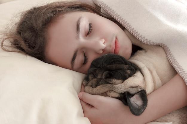 La ragazza abbastanza teenager dorme abbracciando un cane del carlino a letto