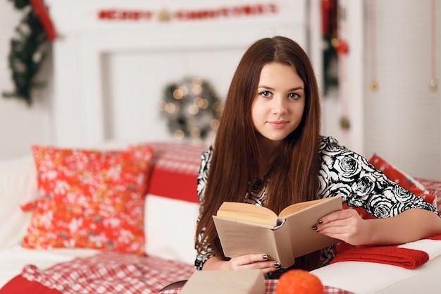Donna abbastanza teenager con capelli lunghi fluenti in interni con decorazioni natalizie