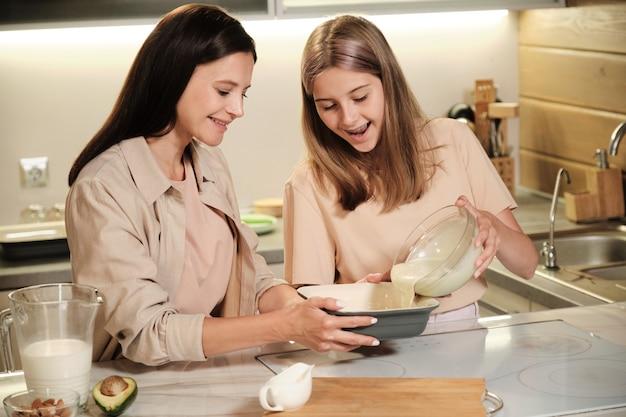 Bella ragazza adolescente versando la miscela di gelato fatto in casa ingredienti in una grande ciotola mentre aiuta la sua mamma con la preparazione