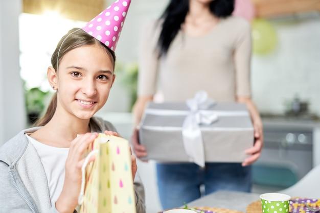 Bella ragazza latina adolescente che sorride alla macchina fotografica mentre tiene in mano una borsa regalo, riceve regali, festeggia il compleanno con la madre a casa. celebrazione, concetto di infanzia. messa a fuoco selettiva