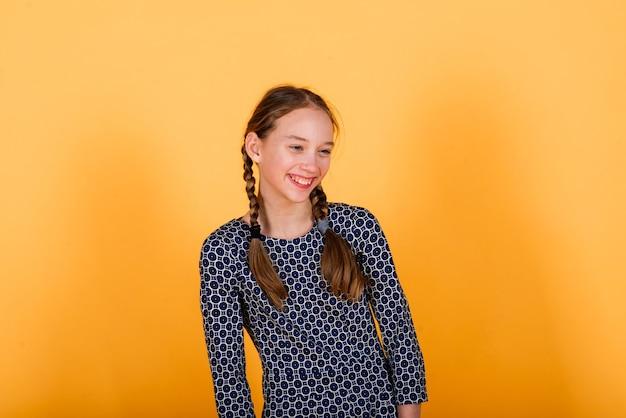 Ragazza graziosa dell'adolescente che sorride sulla macchina fotografica che sembra allegra su fondo giallo. emozioni positive