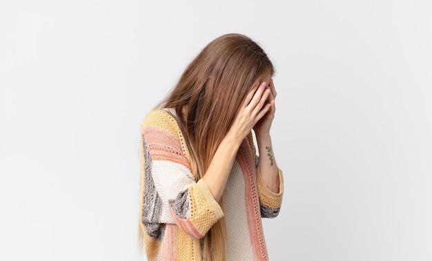 Donna piuttosto magra che copre gli occhi con le mani con uno sguardo triste e frustrato di disperazione, pianto, vista laterale