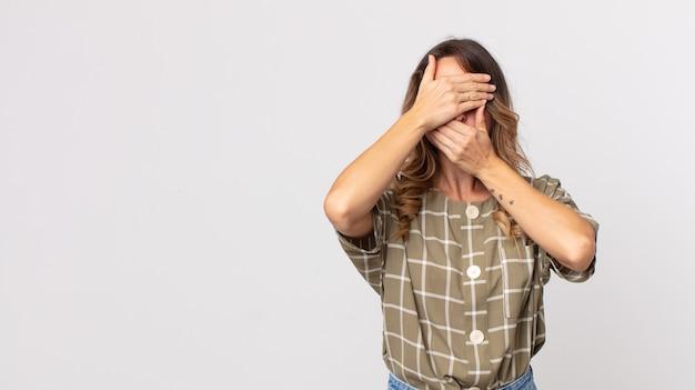 Donna abbastanza magra che copre il viso con entrambe le mani dicendo no alla telecamera! rifiutare le foto o vietare le foto