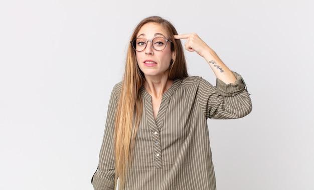 Donna piuttosto magra che si sente confusa e perplessa, mostrando che sei pazzo, pazzo o fuori di testa
