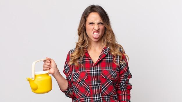 Donna piuttosto magra che si sente disgustata e irritata e fa la linguaccia e tiene in mano una teiera