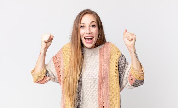 Donna abbastanza magra che si sente felice, positiva e di successo, celebrando la vittoria, i risultati o la buona fortuna
