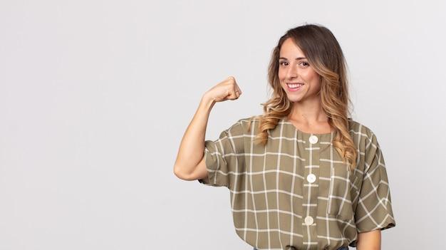 Donna piuttosto magra che si sente felice, soddisfatta e potente, in forma flettente e bicipiti muscolosi, con un aspetto forte dopo la palestra
