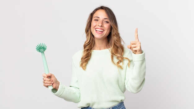 Donna piuttosto magra che si sente un genio felice ed eccitato dopo aver realizzato un'idea e aver tenuto in mano una spazzola per i piatti