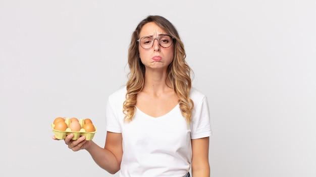 Donna abbastanza magra che si sente triste e piagnucolona con uno sguardo infelice e piange e tiene in mano una scatola di uova