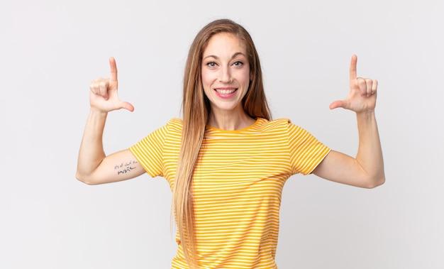 Donna piuttosto magra che incornicia o delinea il proprio sorriso con entrambe le mani, dall'aspetto positivo e felice, concetto di benessere