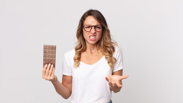 Donna abbastanza magra che sembra arrabbiata, infastidita e frustrata e con in mano una barretta di cioccolato