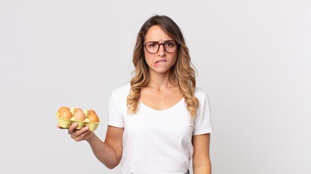Donna abbastanza magra che sembra perplessa e confusa e tiene in mano una scatola di uova