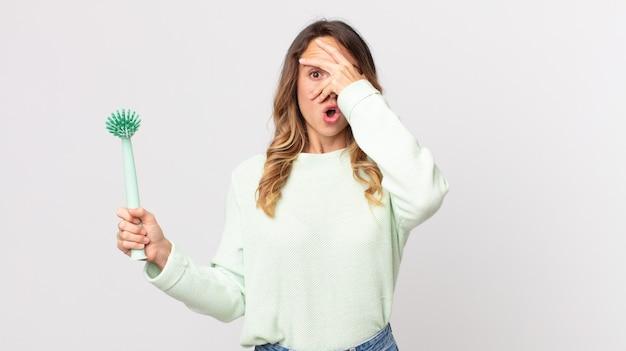 Donna piuttosto magra che sembra scioccata, spaventata o terrorizzata, che copre il viso con la mano e tiene in mano una spazzola per piatti