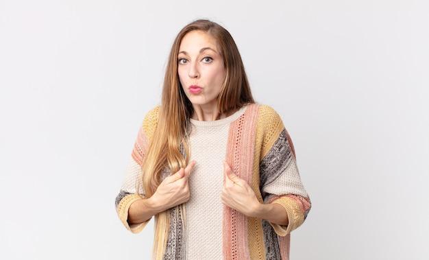 Donna piuttosto magra che indica se stessa con uno sguardo confuso e interrogativo, scioccata e sorpresa di essere scelta