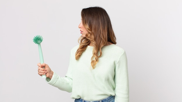 Donna piuttosto magra in vista di profilo che pensa, immagina o sogna ad occhi aperti e tiene in mano una spazzola per piatti
