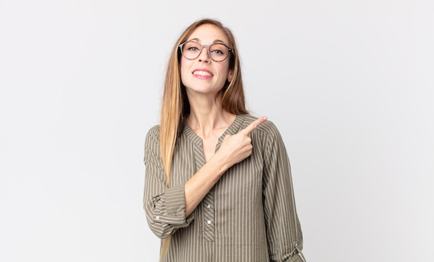 Donna abbastanza magra che sorride allegramente, si sente felice e indica di lato e verso l'alto, mostrando l'oggetto nello spazio della copia
