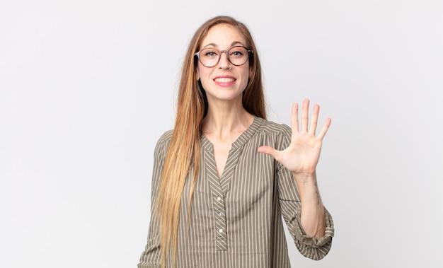 Donna abbastanza magra che sorride e sembra amichevole, mostra il numero cinque o il quinto con la mano in avanti, conto alla rovescia