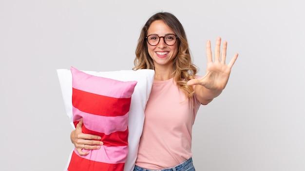 Donna abbastanza magra che sorride e sembra amichevole, mostra il numero cinque in pigiama e tiene in mano un cuscino
