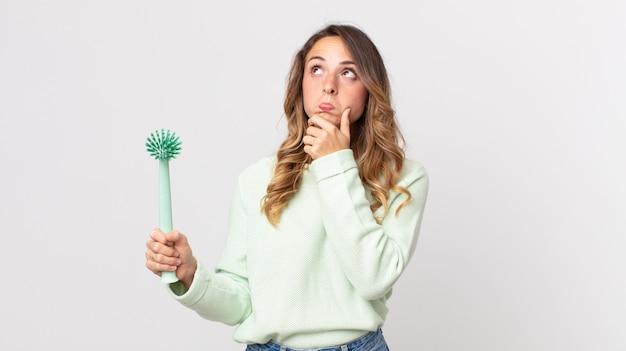 Donna abbastanza magra che pensa, si sente dubbiosa e confusa e tiene in mano una spazzola per i piatti