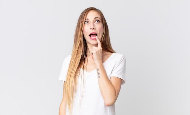 Donna abbastanza magra con sguardo sorpreso, nervoso, preoccupato o spaventato, guardando di lato verso lo spazio della copia