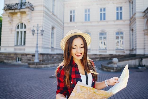 Ragazza graziosa turistica con capelli castani che indossa cappello e camicia rossa, che tiene la mappa al vecchio fondo della città europea e sorridente, in viaggio, ritratto.