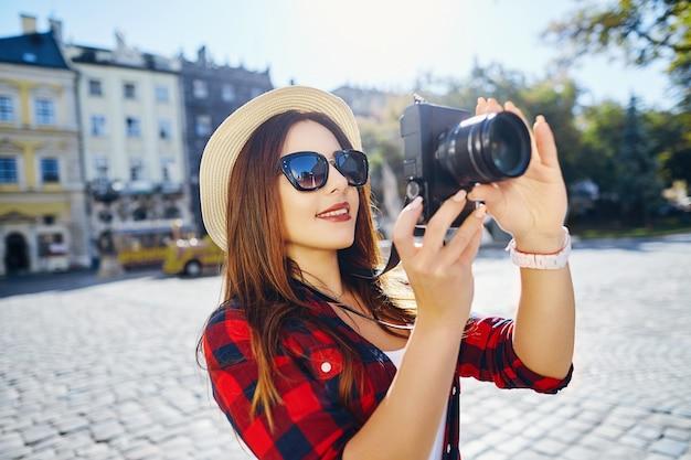 Bella ragazza turistica con capelli castani che indossa un cappello e camicia rossa, facendo foto con la fotocamera a sfondo vecchia città europea e sorridente, viaggiando