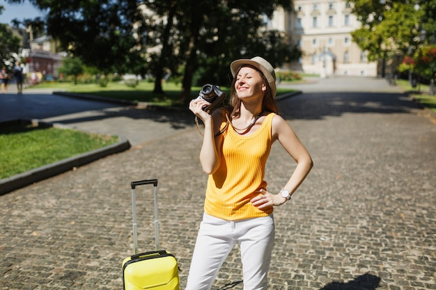 Donna turistica graziosa viaggiatrice con gli occhi chiusi in abiti casual gialli, cappello con valigia tenere retro macchina fotografica vintage all'aperto. ragazza che viaggia all'estero per un weekend. stile di vita del viaggio turistico.