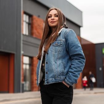 La giovane donna americana abbastanza alla moda con un sorriso carino in giacca di jeans blu è in piedi in città in primavera. modello attraente ragazza moderna in abiti eleganti per strada. moda giovanile americana.