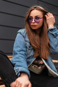 Donna abbastanza urbana giovane hipster raddrizza i capelli che si siede su tavole di legno. ragazza attraente in vestiti di jeans alla moda della gioventù in occhiali viola moda in posa su pallet vintage vicino al muro grigio della città