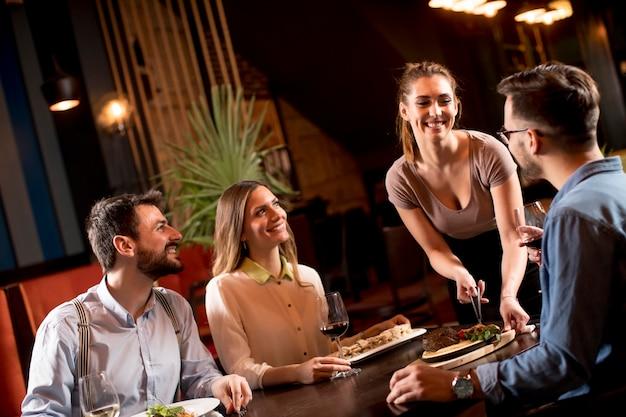 Donna graziosa cameriere che serve un gruppo di amici con il cibo nel ristorante