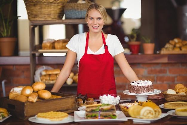 La cameriera carina si chinava su un tavolo da cibo