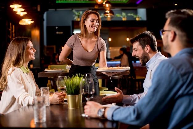 Bella cameriera che serve un gruppo di amici con il cibo nel ristorante