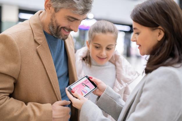 Bella moglie con lo smartphone che mostra a suo marito e alla figlia il nuovo negozio online e sta per fare l'ordine