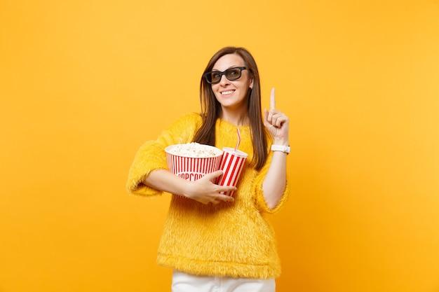 Bella donna in occhiali 3d imax guardando film, tenendo secchio di popcorn tazza di cola o soda puntando il dito indice in alto isolato su sfondo giallo. persone sincere emozioni nel cinema, nello stile di vita.