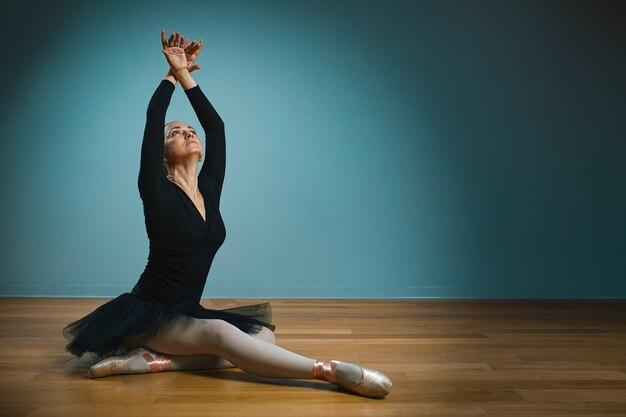 Bella donna ballerina in tutù e punte in costume da bagno nero in posa sulla parete blu. Foto Premium