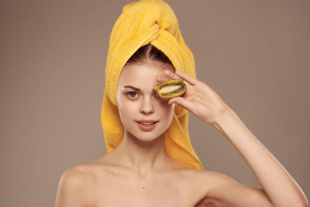 Bella donna spalle nude pelle pulita kiwi in mano ritagliata vista. foto di alta qualità
