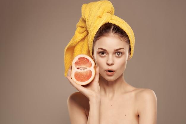 Bella donna spalle nude cura della pelle pompelmo in mano vista ritagliata