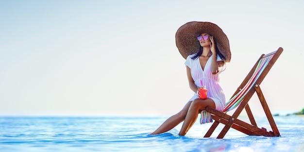 Bella donna con un grande cappello di paglia che si rilassa su una spiaggia con sdraio e beve succo rinfrescante estate vacatio...