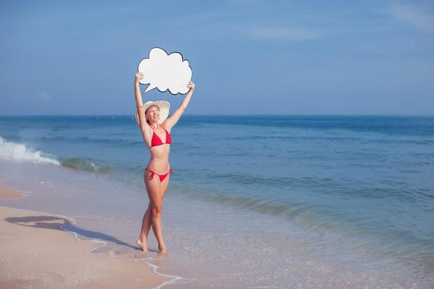 Donna graziosa in bikini con discorso della bolla in mani sulla spiaggia