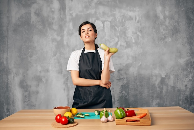 Donna graziosa in verdure nere dei grembiuli che cucinano a casa