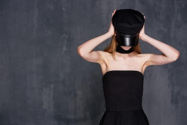 Bella donna in abito nero cosmetici casa di lusso sfondo scuro