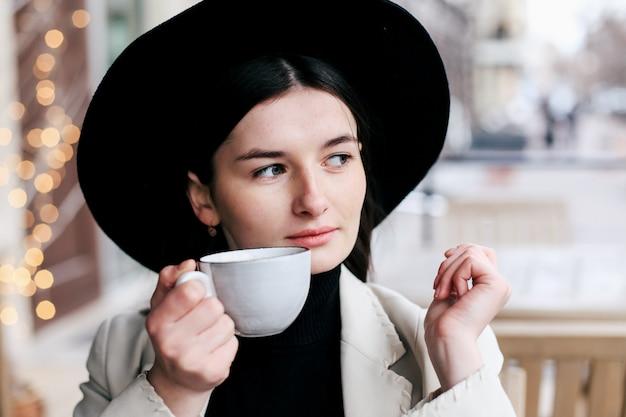 Donna graziosa in cappello nero dei pantaloni a vita bassa della fedora che gode del caffè in una caffetteria